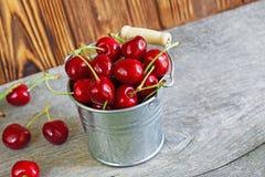 Cherrys de un ith del cubo en fondo de madera Fotos de archivo libres de regalías