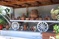 Chersonissos, Cyprus, Greece - 31.07.2013: clay pots and dishes on a wooden cart royalty free stock photos