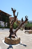 Chersonissos, Cyprus, Greece - 31.07.2013: sculpture of wood in the middle of the garden of plants and flowers in Crete stock images