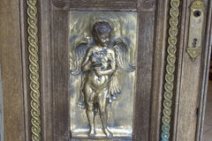 Cherub bas relief on wooden door Royalty Free Stock Image