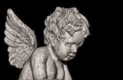 Cherub on black. Stone cherub given illustrative look. Contains clipping path Stock Photo