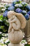 Cherub dreaming in the garden stock photo