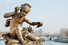 Cherub on Pont Alexandre III bridge in Paris. Bronze statue of a cherub on Pont Alexandre III bridge in Paris with the River Seine and The Louvre in the Royalty Free Stock Photos