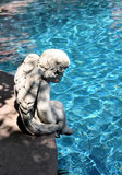 Cherub at pool side. Cement cherub sits pensively at the side of a swimming pool Royalty Free Stock Photography