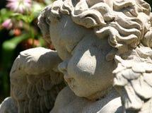 Cherub rock. Cherub statue head in profile in a garden Royalty Free Stock Photos
