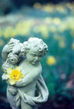 Cherub Rock. A stone cherub statue stands over a pond Royalty Free Stock Images