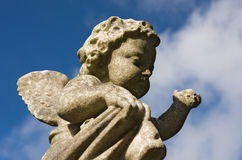 Cherub statue. Small statue of a cherub shot against a deep blue cloudy sky Royalty Free Stock Photography