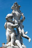 Cherub statue in front of the leaning tower in Pisa, Tuscany, Italy. Fontana dei Putti, fountain with the angels, Cherub marble sculpture and blue sky in Stock Image