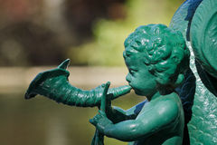 Cherub Statue. A Green Cherub Statue Playing a Musical Instrument Royalty Free Stock Photography