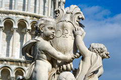 Cherub statue. Pisa, Italy. Cherub statue that sits on the Field of Miracles in Pisa Italy with the leaning tower in the background. Detail royalty free stock image