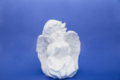 Cherub statuette  on blue Stock Photography