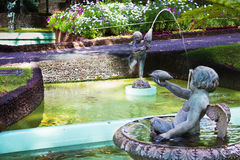 Cherubs water fountain in tropical garden Stock Photo