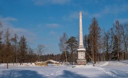 Chesma obelisk in Gatchina Park. Sunny winter`s day. In the background on the left is the Humpbacked Bridge stock images