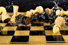 Chess. Many chessmen fall on chessboard, in water, drops fly to the different sides Stock Photography