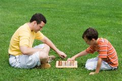 Chess. Father and son playing chess in a park Royalty Free Stock Photos