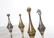 Chess pieces on chessboard. Details of several shiny, metallic silver and gold chess pieces on a chessboard Stock Images
