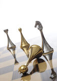 Chess pieces on chessboard. Shiny, metallic silver and gold chess pieces on a reflective chessboard Royalty Free Stock Photo