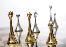 Chessboard with king in focus. A chessboard with the dark king in focus, surrounded by queen and a pawn Royalty Free Stock Photos