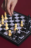 Chess. Hand moving a piece in a game of chess Stock Photography