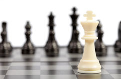 Chess. White and black chessmen on a chessboard Royalty Free Stock Images