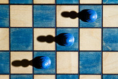 Chess. A chessboard with three pawns, shot from above and lit from one side, so that the pieces drop shadows by which they reveal their shape Royalty Free Stock Images