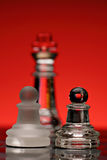 Chess. Strategic games; chess; two pawns of opposite color; king out of focus in background Royalty Free Stock Photo