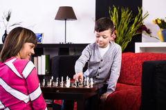Chess. Young women and a boy playing chess in the own home Stock Images
