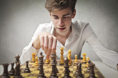 Chess. Handsome young man playing chess royalty free stock photography