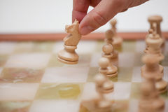 Chess. A chess player moves his knight Royalty Free Stock Photography