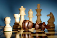 Chess. A game of chess comes to an end. The black king is checkmated, and white is victorious Royalty Free Stock Photo