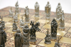 Chess. Antique wooden and 'mother of pearl' chess board with pewter chess pieces on it Stock Image