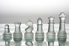 Chess. Glass chess pieces against white color background Royalty Free Stock Photo