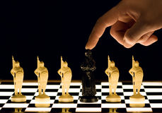 Chess. Mans finger and white queen Stock Image