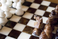 Chess. Close up of chess on a marble chessboard focus on brown horse stock photography