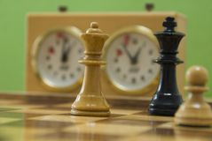 Chess. Black king, white queen and white knight on chess board with clock, time running out Royalty Free Stock Photo