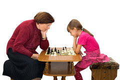 Chess. The grandmother and the granddaughter play a chess Stock Photos