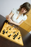 Chess. Young white caucasian woman plays chess. Game takes place at home at brown table royalty free stock photo