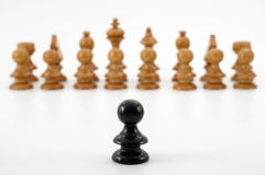 Chess. Black pawn alone against oponent army with shallow depth of field Royalty Free Stock Photos