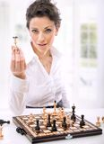 Chess. A young woman holding chess pieces royalty free stock image