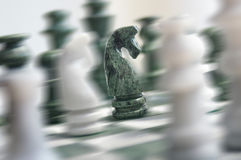 Chess action. Chess set, all pieces are blurred except sharp the Knight in the center Royalty Free Stock Photography