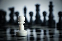 Chess against. One chess is staying against full army of chess pieces Stock Photography