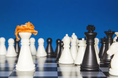 Chess as a policy 15. Chess as a policy. A lone white figure with red hair against a black figure with a team. The public looks from the outside stock photography
