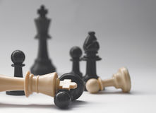 Chess battle - fallen king - plastic chess pieces - kings, bishop, pawns Stock Images