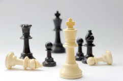 Chess battle - plastic chess pieces - king, queen, bishop, pawns - selective focus Royalty Free Stock Photography