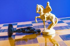 Chess on black background. White horse stands in front of a pawn Royalty Free Stock Images