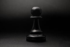 Chess. Black pawn on a black background. royalty free stock photos