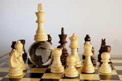 Chess board. Globe is placed in between the chess board and the king is on top of Globe Stock Photos