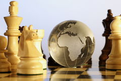 Chess board. Globe is placed in between the chess pieces Royalty Free Stock Image