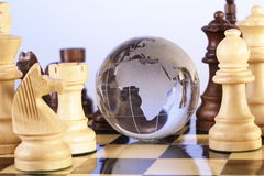 Chess board. Globe is placed in between the chess pieces Royalty Free Stock Photo