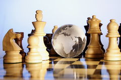Chess board. Globe is placed in between the chess pieces Stock Photo
